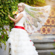 Happy bride in white dress near the green wall — Stock Photo #17822763