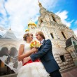 Bride and groom are hugging near the church building - Stock Photo