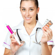 Woman doctor in a white coat with syringe and pills — Stock Photo