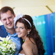 Bride and groom is laughing near the glass — Stock Photo