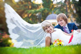 Happy couple are lying on the green grass — Stock Photo