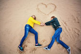 Couple are lying on the sand with a heart — Stock Photo