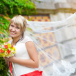 Happy bride in white dress near the green wall - Stock Photo