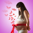 Pregnant woman with red butterfly . isolated - Stock Photo