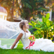 Bride in a white dress is lying on the green grass — Stock Photo