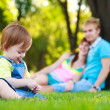Baby playing with parents in a beautiful summer park — Stock Photo