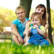 Family on a green lawn in park — Stock Photo