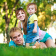 Stock Photo: Baby with parents in a green summer park