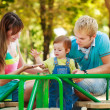 Portret of happy family on a playground — Stockfoto
