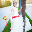 Happy bride in white dress near the palm tree — Stock Photo