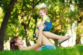 Funny baby with mom in a greenl summer park — Stock Photo