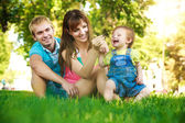 Happy family on a green lawn in park — Stock Photo