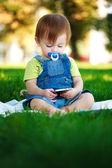 Baby spielt mit dem telefon auf das grüne gras — Stockfoto