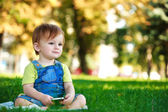 Cute baby is playing with phone on the green grass — Stock Photo
