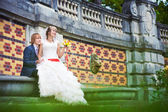 Bride and groom are sitting near the patterned wall — Stock Photo