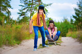 Funny couplel are sledding at summer — Stock Photo