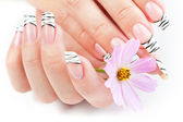 Hands with striped manicure relaxing with flowers — Stock Photo
