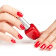 Hands with red manicure and nail polish bottle isolated — Stock Photo #19160277