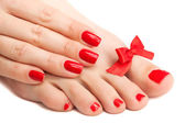 Red manicure and pedicure with a bow. isolated — Stock Photo