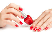 Hands with red manicure and nail polish bottle isolated — Stock Photo