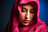 Krásná mladá žena s červenými závoj kolem obličeje — Stock fotografie