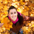 Cute girl on a background of autumn leafs. top view — Stock Photo #19266765