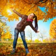Girl on a background of sky and autumn leafs — Stock Photo #19266857