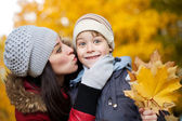 Happy Mom is kissing her son in a yellow autumn park — Stock Photo