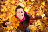 Cute girl on a background of autumn leafs. top view — Stock Photo