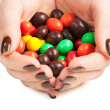 Stock Photo: Female hands full of colored candy