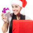 Happy woman in a Santa Claus hat with lots of gifts — Stock Photo #19552289