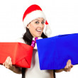 Happy girl in a Santa Claus hat with lots of gifts — Stock Photo #19552285