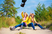 Funny couple in caps with ear flaps with sled — Stock Photo