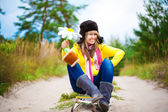 Funny girl in cap with ear flaps and flower — Stock Photo