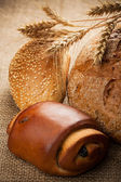 Assortment of baked bread on burlap background — Stockfoto