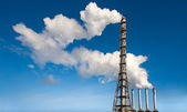 Toxic industrial smoke from chimney on blue sky — Stock Photo