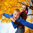 Happy mom and son are playing in the autumn park — Stock Photo #21980647