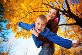 Happy mom and son are playing in the autumn park — Stock Photo