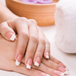 Manicured female hands with aromatic candles and towel. Spa — Stock Photo #22108771