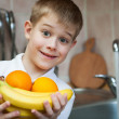Stock Photo: Little boy is washing fruit in kitchen