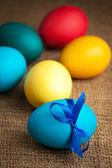Color de los huevos de pascua en el fondo de arpillera — Foto de Stock