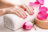 Beautiful pink manicure with fragrant rose petals and towel. Spa — Stock Photo