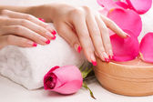 Female hands with fragrant rose petals and towel. Spa — Stock Photo
