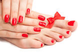 Red manicure and pedicure with a bow — Stock Photo