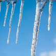 Big Icicles on the roof against a blue sky — Stock Photo