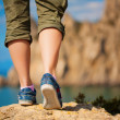 Tourism. female feet in sneakers — Stock Photo