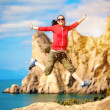 Young woman is jumping over mountain peak — Stock Photo