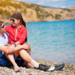 Happy couple are sittting on the beach - Stock Photo