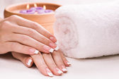 Vrouwelijke handen met aromatische kaarsen en handdoek. spa — Stockfoto