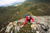 Woman climber is climbing on a rock — Stock Photo